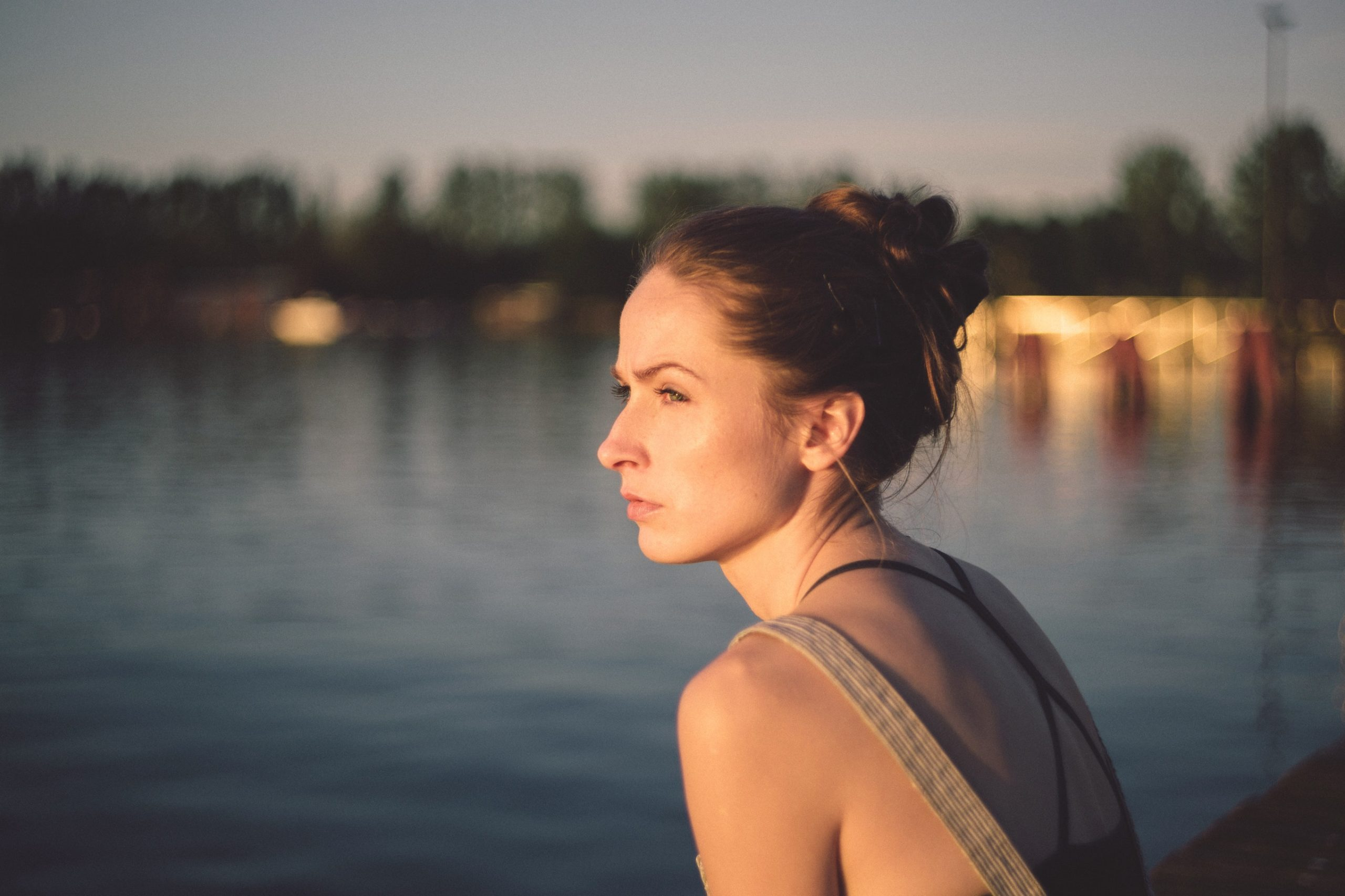 Woman looking out at water to show comparative suffering